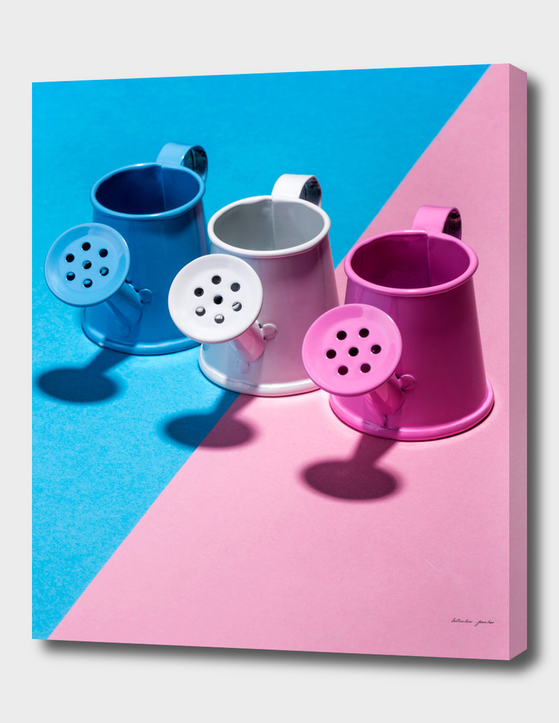 Three small watering cans on a colored background