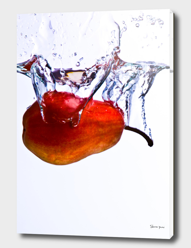Pear falls into water with a splash on white background