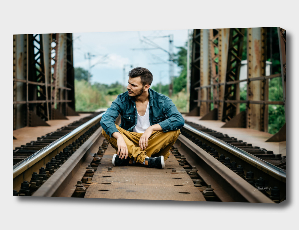 Portrait of young man sitting on the railroad bridge