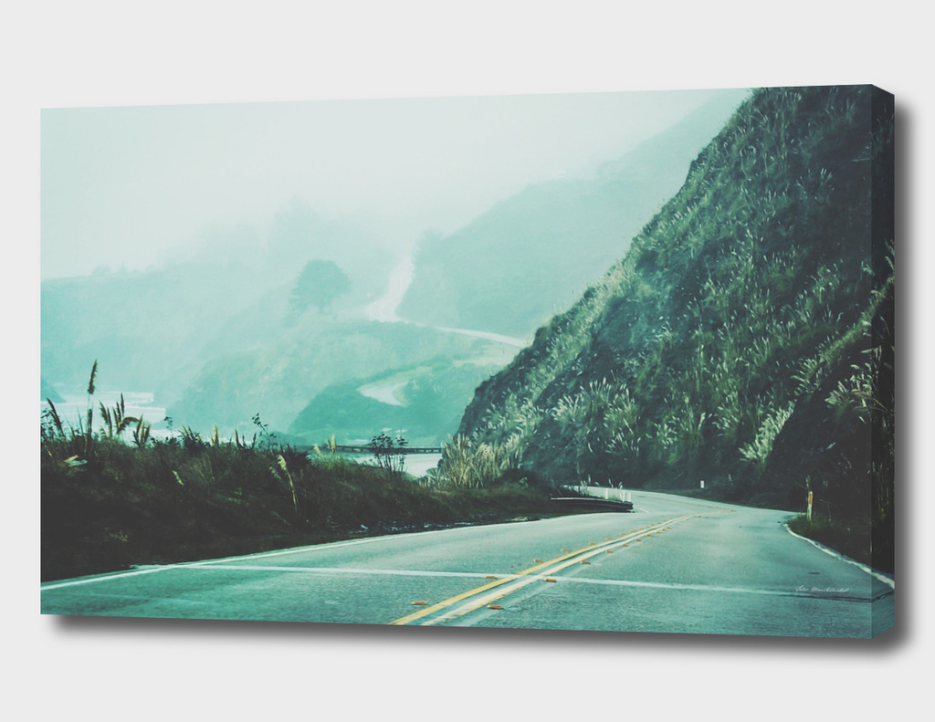 road with mountain view and foggy sky