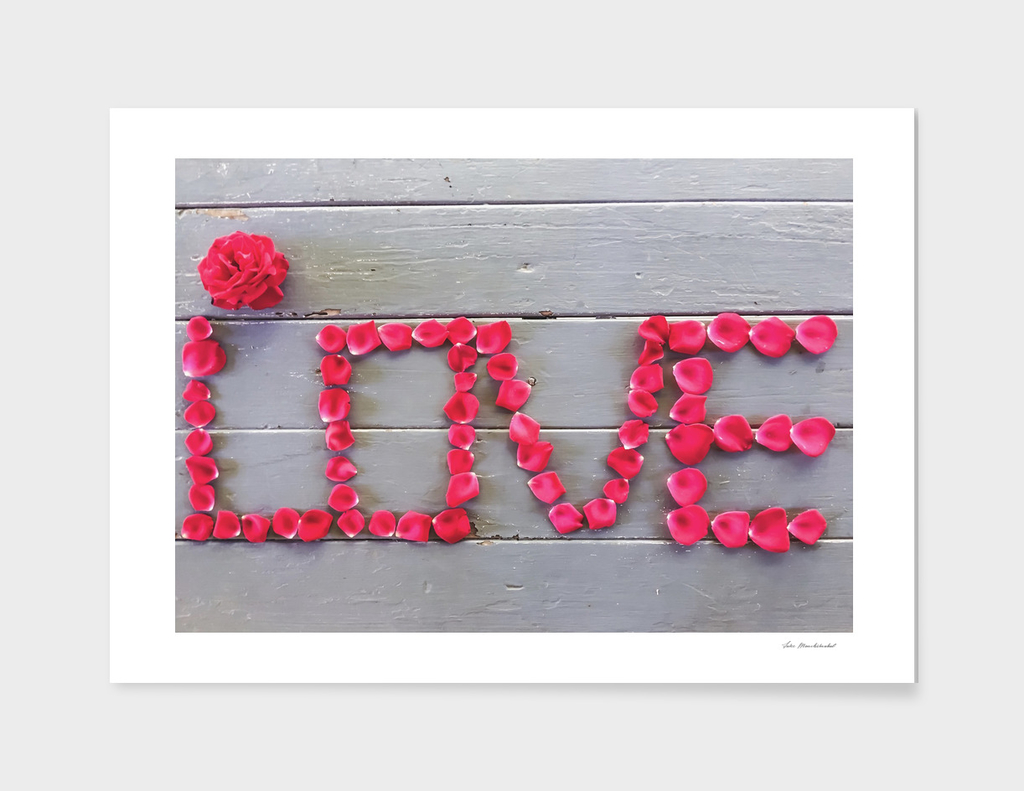 LOVE alphabet with red rose on the wooden table