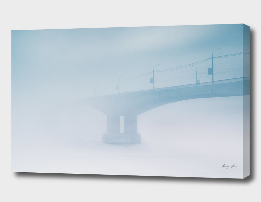 Bridge in winter fog on morning Russia