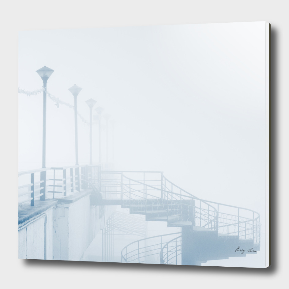 Lantern in fog with spiral staircase on pier