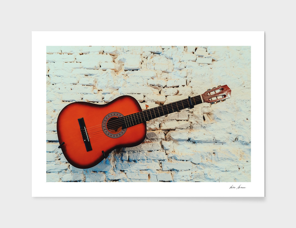 Vintage Guitar On White Brick Wall