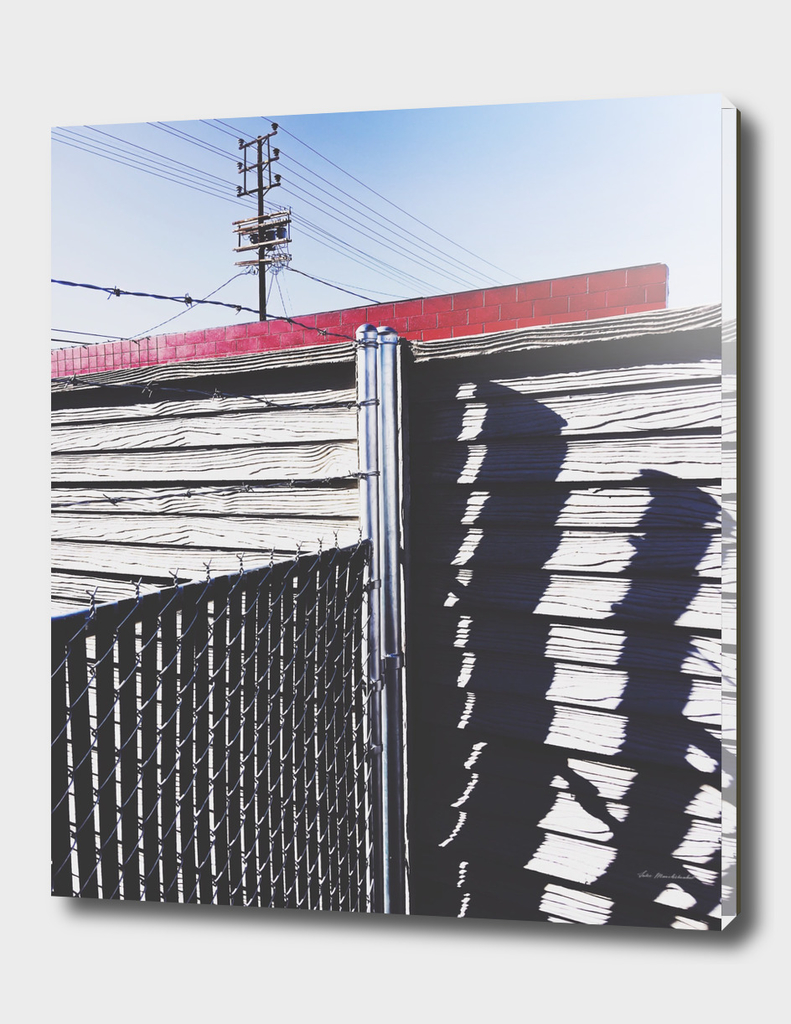 steel fence and wooden fence with red building in the city
