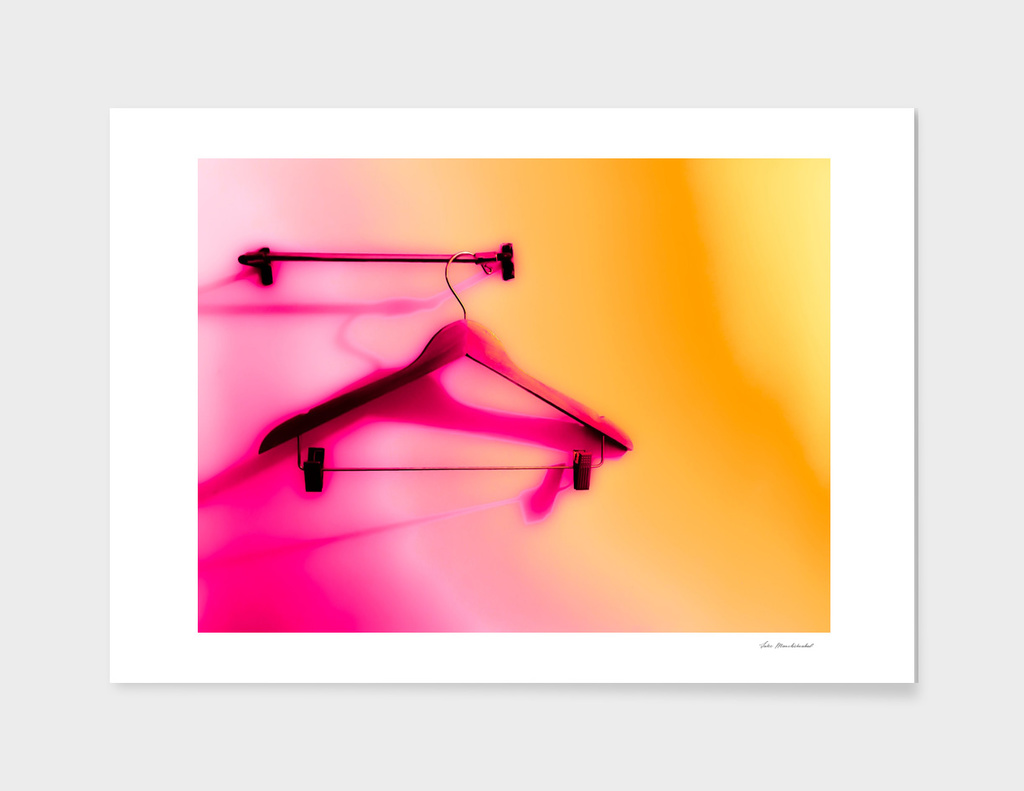 wood hanger with pink and orange background