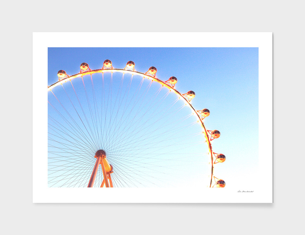 orange Ferris Wheel in the city with blue sky