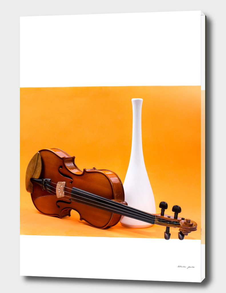 Still life with violin and white vase on an orange