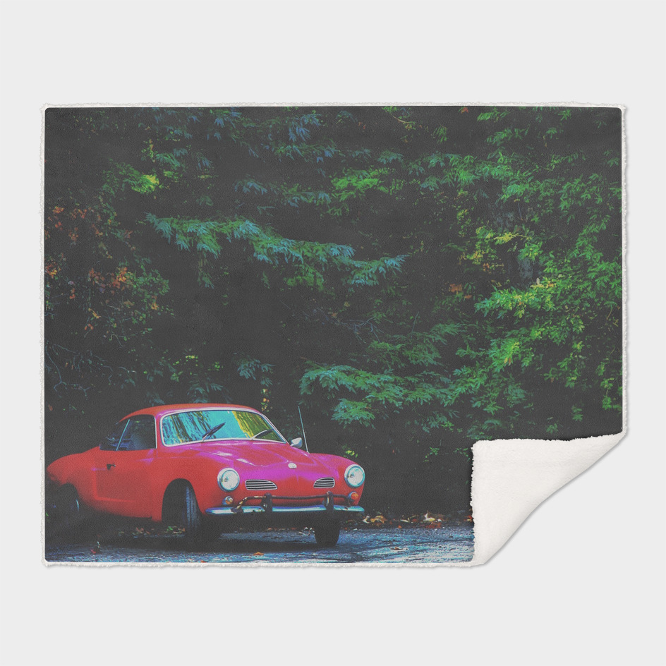 red classic car in the forest with green tree background