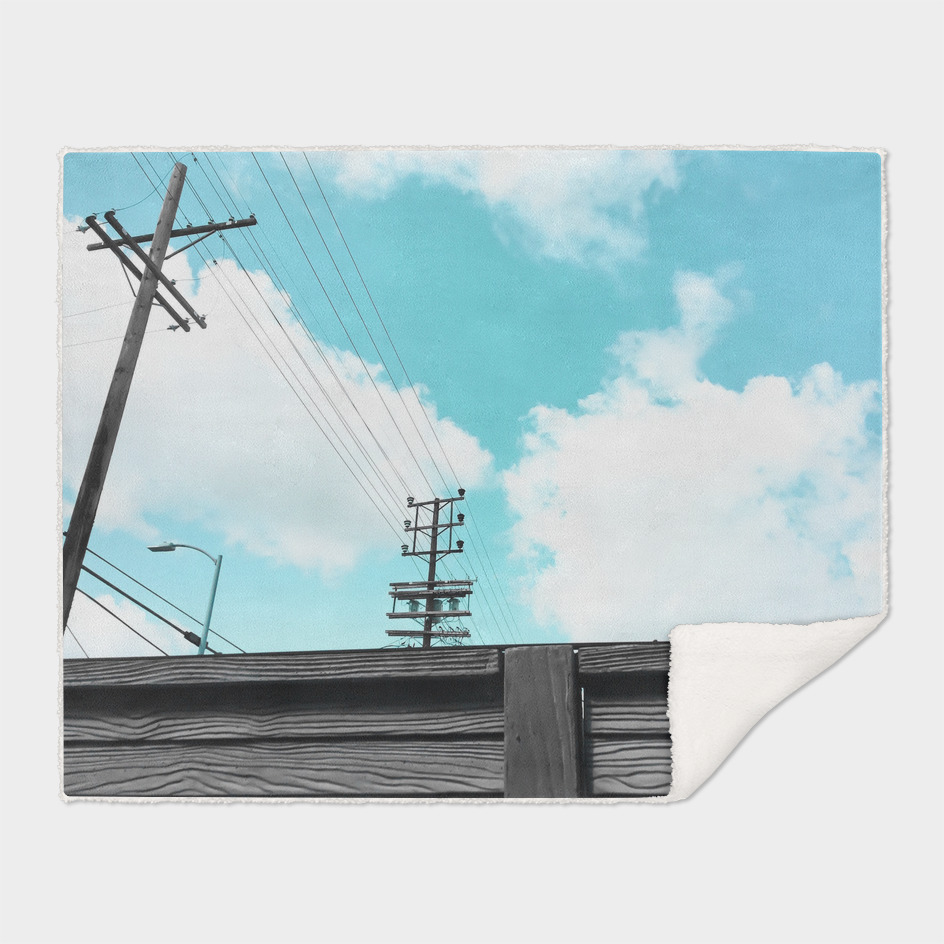 electric pole with wood wall and blue cloudy sky in the city
