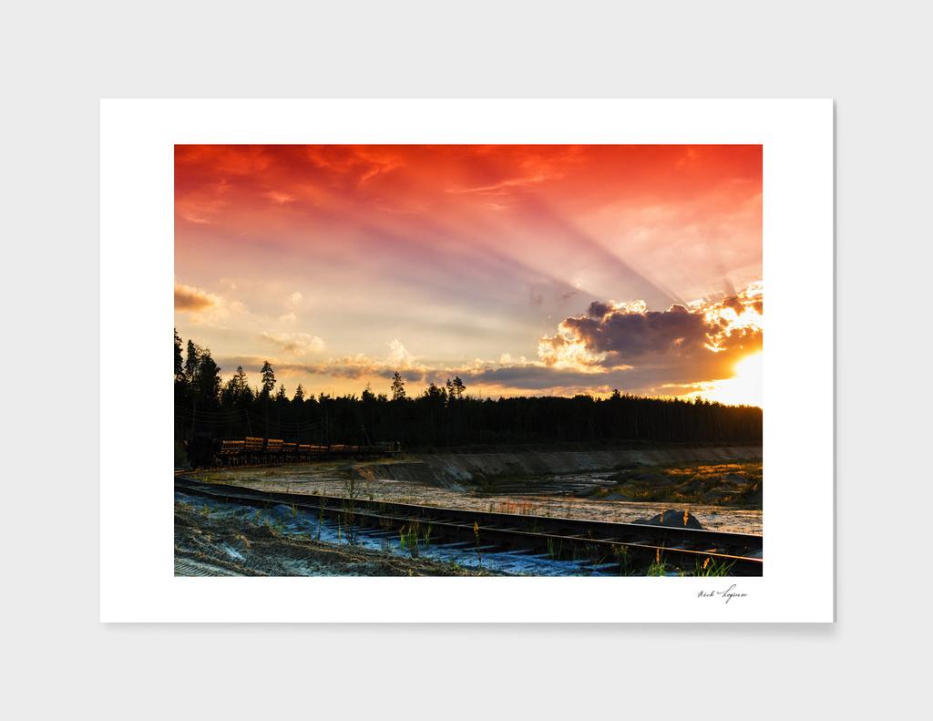 Cargo train heading to dramatic sunset